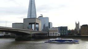 Passagierstoeristen op de Rivier van Theems, Rode dubbele dekbus op de Brug van Londen en de Scherftoren stock footage