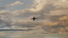 Passagiersvliegtuig die bij zonsondergang tegen de achtergrond van zeer mooie wolken opstijgen Royalty-vrije Stock Afbeeldingen