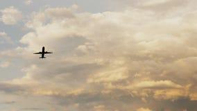 Passagiersvliegtuig die bij zonsondergang tegen de achtergrond van zeer mooie wolken opstijgen Royalty-vrije Stock Foto's