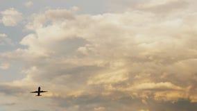 Passagiersvliegtuig die bij zonsondergang tegen de achtergrond van zeer mooie wolken opstijgen Stock Foto's