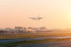 Passagiersvliegtuig die in de luchthaven van de hemelzonsondergang van start gaan stock afbeeldingen