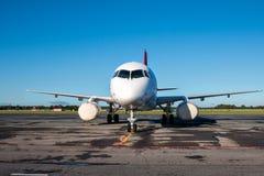 Passagiersvliegtuig in een parkeerterrein met gehulde motoren en verbonden met een externe voeding stock foto's