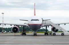 Passagiersvliegtuig in het parkeren bij de luchthaven met een voorwaartse neus en een doorgang Stock Fotografie