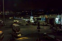 Passagiersvliegtuig op baan dichtbij de terminal in een luchthaven bij nacht De bemanning die van het luchthavenland de vluchtdie stock fotografie