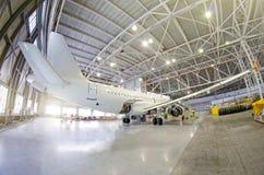 Passagiersvliegtuig op onderhoud van motor, fuselage en op hulpkrachteenheid controleer reparatie in luchthavenhangaar Vliegtuige stock foto