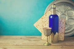 Passahfesthintergrund mit Matzo und Wein auf hölzerner Weinlesetabelle Sederteller mit hebräischem Text Stockbilder