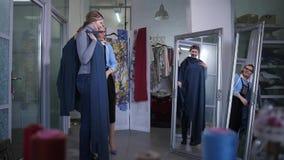 Passande klänning för klient i atelier arkivfilmer