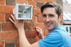 Passande säkerhetsljus för man som inhyser väggen Royaltyfri Fotografi