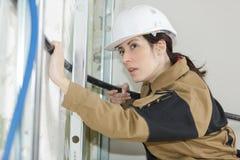 Passande trumma för kvinnlig elektriker i vägg på konstruktionsplatsen Arkivfoton