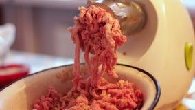 Passando a mistura triturada da carne e do vegetal através do picador em casa em casa filme