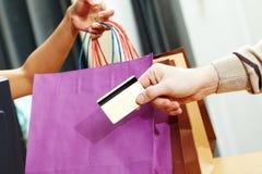 Passando o cartão de crédito Imagens de Stock