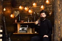 Passando o grande tempo em casa O homem com barba guarda o vidro da bebida sazonal quente ferventada com especiarias do vinho O i Fotos de Stock