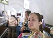 Passanger de las chicas jóvenes en la escalera móvil en el subterráneo Imagen de archivo libre de regalías