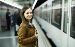 Passanger femenino alegre que se coloca en la plataforma de llegada fotografía de archivo libre de regalías