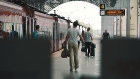 Passangers людей при сумки идя вдоль красного поезда на железнодорожной станции сток-видео