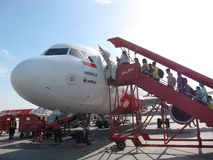 Passangers boarding Air Asia plane. Passangers boarding AirAsia plane using boarding stairs on Kuala Lumpur Low Cost Carrier Terminal royalty free stock photo