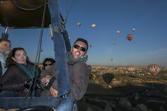 Passangers ombord en ballong för varm luft tycker om det härliga landskapet ovanför Goreme i den Cappadocia regionen av Turkiet arkivfoton