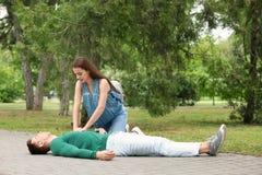 Passant, der CPR auf Mann mit Herzinfarkt, draußen durchführt stockfotografie