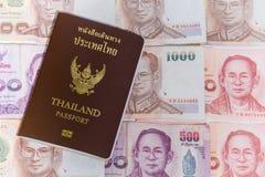 Passaporte de Tailândia com as cédulas e as moedas do baht tailandês do fundo Fotografia de Stock Royalty Free