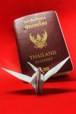 Passaporte de Tailândia e pássaro do papel no fundo vermelho Fotos de Stock Royalty Free