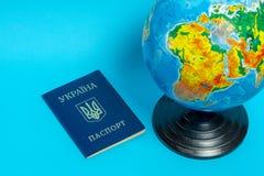 Passaporte de um cidad?o de Ucr?nia perto do globo em um fundo azul fotografia de stock