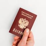 Passaporte do russo à disposição em um fundo branco Imagem de Stock