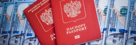 Passaporte dois vermelho no fundo de cem notas de dólar Projeto azul foto de stock royalty free
