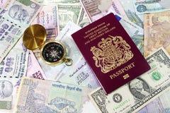 Passaporte e compasso em contas de moeda Fotos de Stock Royalty Free