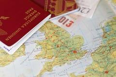 Passaporte e conta inglesa da libra em um mapa de Reino Unido Fotografia de Stock