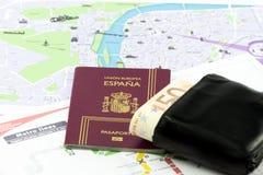 Passaporte espanhol com moeda da União Europeia em uma carteira e em um mapa Imagens de Stock