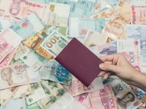 Passaporte fêmea do curso da terra arrendada da mão com cem dólares americanos para dentro no fundo da textura do dinheiro de Ási Imagens de Stock
