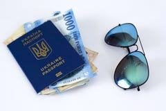 passaporte internacional de Ucr?nia, de dinheiro e de vidros em um fundo branco ?O conceito do curso sem coisas desnecess?rias ? imagem de stock royalty free