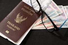 Passaporte tailandês com passagem de embarque, dinheiro do kyat de Myanmar e monóculos no assoalho preto fotos de stock royalty free