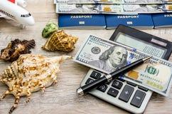 Passaportes, dólares, conchas do mar e um avião em um fundo de madeira foto de stock royalty free