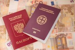 Passaportes do grego e do russo no fundo das cédulas Viagem e finança Imagens de Stock