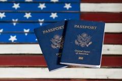 Passaportes dos EUA na tabela de vidro sobre a bandeira dos E.U. Imagens de Stock Royalty Free