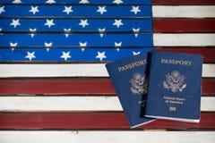 Passaportes dos EUA na tabela de vidro sobre a bandeira dos E.U. Fotografia de Stock Royalty Free