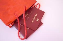 Passaporti come regalo Passaporti in una borsa rossa del regalo fotografia stock