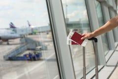 Passaporti della tenuta dell'uomo e passaporto di imbarco a Immagini Stock