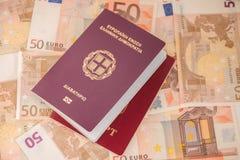 Passaporti greci e russi sul fondo delle banconote Viaggio e finanza immagini stock