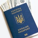 Passaporto biometrico dell'Ucraina con le banconote in dollari su un fondo bianco Immagini Stock