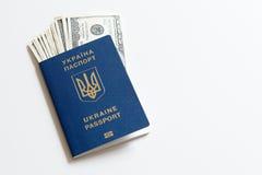 Passaporto biometrico dell'Ucraina con le banconote in dollari su un fondo bianco Immagine Stock