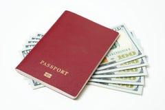 Passaporto biometrico straniero con i dollari isolati su un fondo bianco Cinque fatture per cento dollari Il concetto di immagini stock libere da diritti