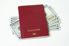 Passaporto biometrico straniero con i dollari isolati su un fondo bianco Cinque fatture per cento dollari Il concetto di fotografia stock
