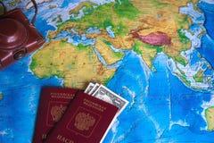 Passaporto con i dollari e una macchina fotografica sulla mappa di mondo Fotografia Stock
