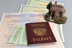 Passaporto con il modello della casa e materno russi, della nascita e della penna Immagini Stock