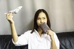 Passaporto ed aeroplano della tenuta della donna immagini stock