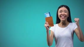 Passaporto emozionante della tenuta della donna con i biglietti a disposizione, vincendo giro di vacanza video d archivio