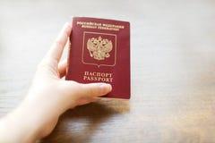 Passaporto russo a disposizione su fondo di legno immagine stock libera da diritti