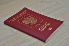 Passaporto russo rosso sulla superficie di legno con il passaporto di titoli e sulla Federazione Russa nell'alfabeto cirillico Immagini Stock Libere da Diritti